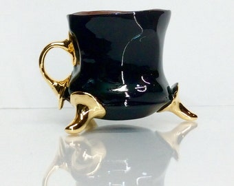 black mug with gold and one finger handle