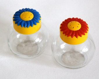 Vintage salt and pepper glass shakers with plastic sunflower design lids