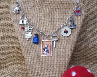 "Alice In Wonderland Charm Necklace with White Rabbit, Locks, Keys, Chess Pieces, and Real Blue Glass ""Eat Me"" Bottle 19.5 Inches Length"