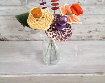 yellow orange and purple button flower bottle bouquet
