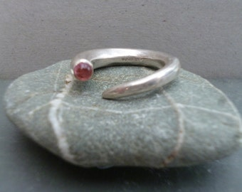 Sterling silver open ring set with a pink tourmaline, currently size N, can be adjusted