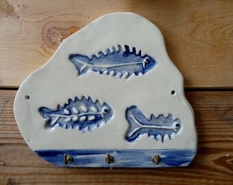 decorated with 3 blue fish - white ceramic plate hanging towels or kitchen utensils.