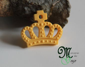 "Teething ring. Pale yellow ""Crown"" shape."