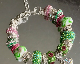 Pink and green crystal silver bracelet with dangling heart charm.