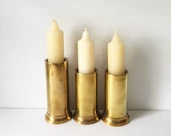 Three Brass Cylinder Candle Holders With Cream Colored Candles Included