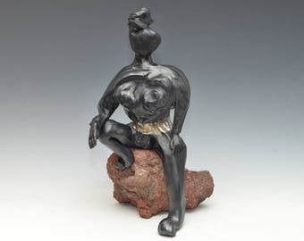 Black and Gold Abstract Buddha Kwan Yin Sitting on a Rock