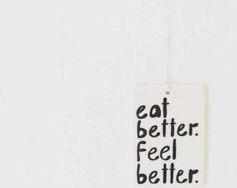 porcelain wall tag screenprinted text eat better. feel better.