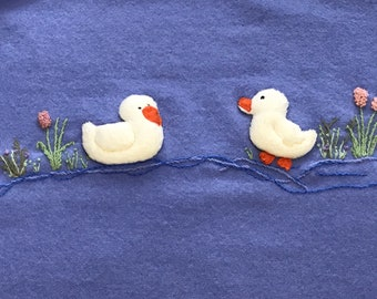 Wool cotton backed satin bound baby blanket hand sculptured ducks and hand embroidered.