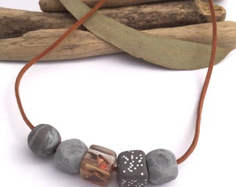 Eco-resin and clay bead necklace in marble greys, charcoal with glitter, and clear with embedded wood and copper foil.