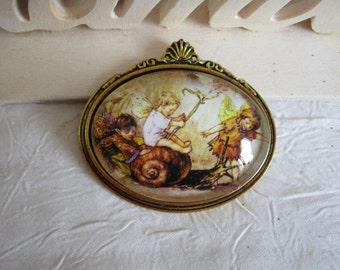 """Broche en métal doré  """"Trois petits elfes des fleurs jouent avec un escargot"""""""