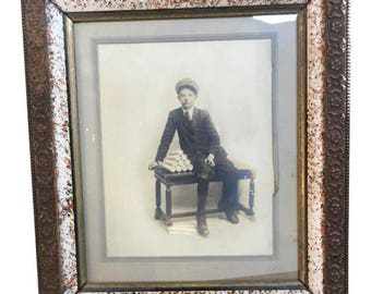 Edwardian framed black & white photograph of a young boy seated on a bench, Circa 1915.
