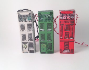 Trio of hand-printed little wooden Christmas house ornaments packaged with Santa gift tag.