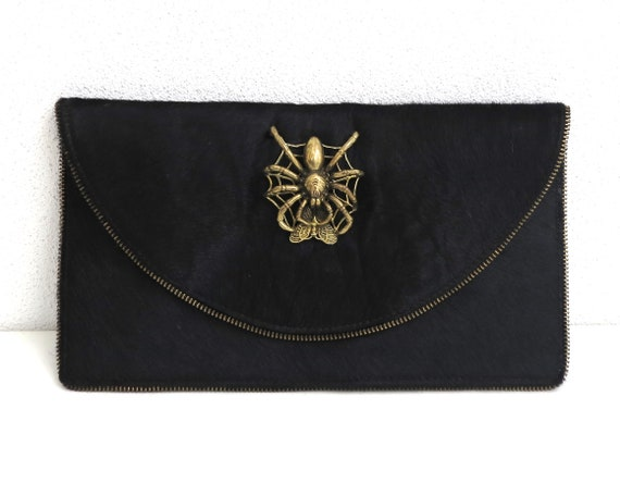 Black leather cowhide clutch with 3-D gold metal spider and butterfly decoration, half zips decorate the edges, unusual, Goth style
