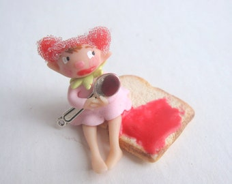 Miniature fairy figurine on slice of toast with jam