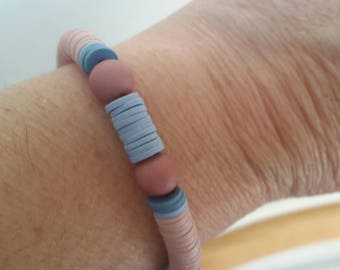 A blue flat round beads of pink bracelet with two plastic beads round in pink color very light on the wrist