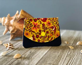 Women's three pocket wallet brightly colored with yellows and red's on a navy blue background.