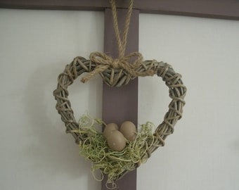 heart with decorative spring rattan with nest and eggs