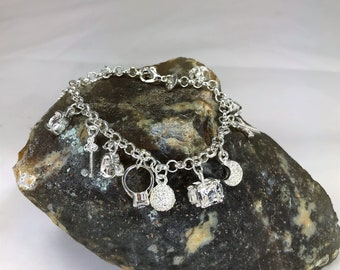 A Beautiful 925 Silver Multi charm Bracelet. Matching Necklace Also Available