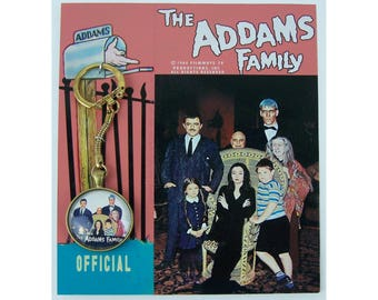1964 Filmways tv Productions The Official ADDAMS FAMILY KEYCHAIN on display card reproduction... very rare even for a replica