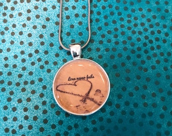 Love never fails heart on the sand necklace