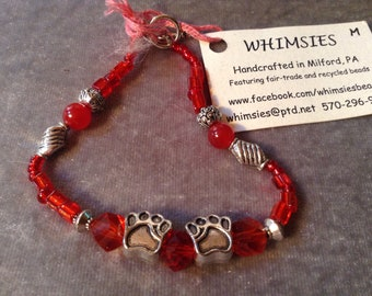 Glass beaded bracelet, size MEDIUM, red mix, dog or cat paws. Boho, hippie, fair trade, gift, free shipping. Made in USA.