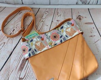 Rubie Faux Leather Mustard crossbody with cotton and steel August lion accent fabric.