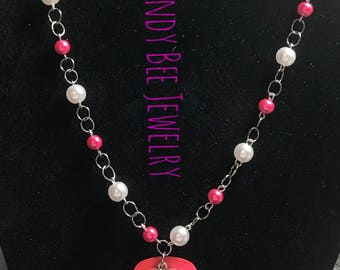 Pink and white beaded necklace with pink guitar pick with a silver book charm