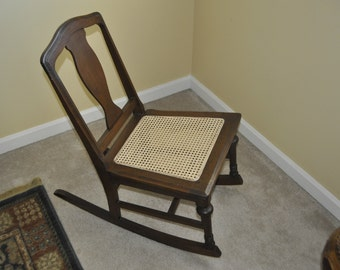 Vintage cane rocking chair in an elegant finish. Dark decorative design with a cane weaved seat.