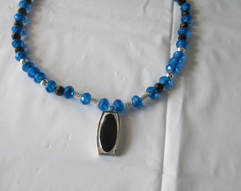 Black/silver pendant on deep blue necklace