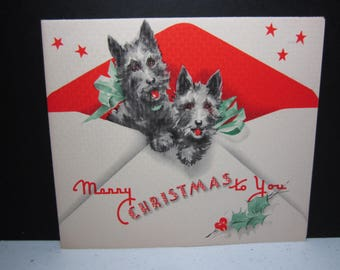 Adorable 1930's-40's art deco christmas card shows 2 black scotty dogs wearing matching green ribbons peeking out of a red envelope