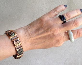 Mid Century Copper Panel Bracelet With Random Assortment of Images Mask Swordfish Lock