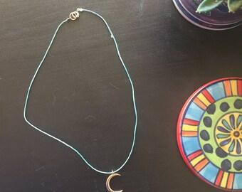 Gold crescent moon choker on aqua cording