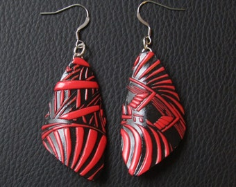 Textured red earrings on black background. Dangling earrings. Lightweight earrings.