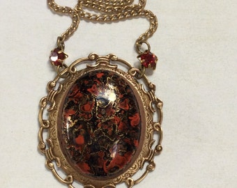Vintage red and black patterned pendant. Ornate brass setting. Vintage siam ruby rhinestones.