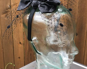 Party headband with two mini silk bows. Adorned with a birdcage veil. Black. One size. Add sequins for your own custom shine!