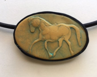Trotting horse pendant, gold with green patina and black frame polymer clay pendant.