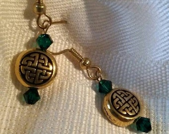 Emerald green and gold plated pierced earrings with Celtic knot beads.