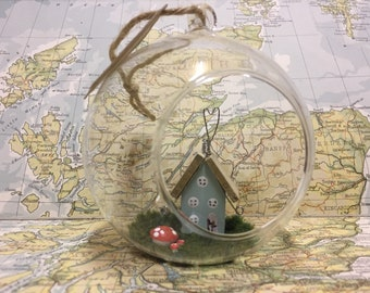 Glass bauble with wooden fairy house and toadstools