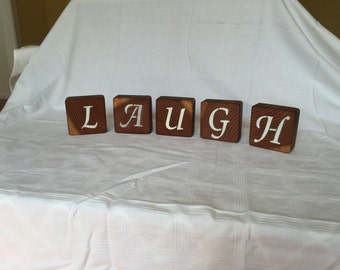 Handmade decorative blocks spelling laugh