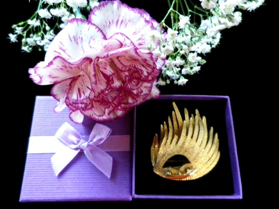 Gold tone brooch or lapel pin in a wing design, with gift box