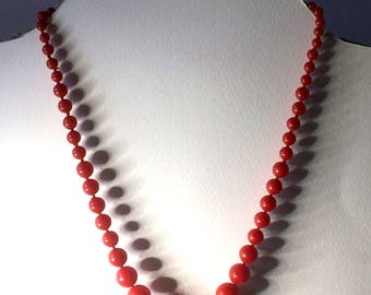 Beaded necklace with red resin rose tied with a brass topped with a red cabochon clasp