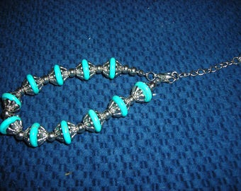 Adjustable silver and turquoise bracelet with lobster clasp closure with an  adjustable chain.