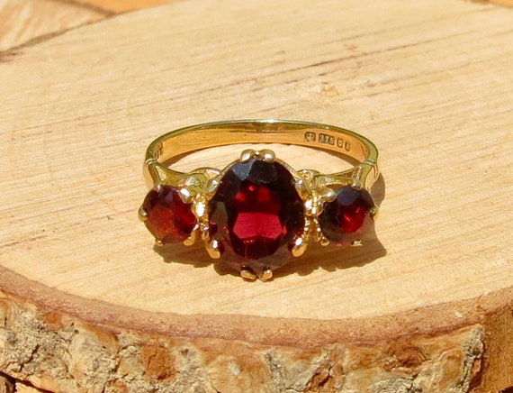 A vintage 1970s 9K yellow gold ring with a graduated red garnets.