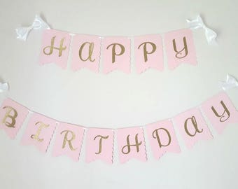 Happy birthday banner in pink flags, gold letters & white satin ribbon bows. Pink and gold birtday. Princess birthday. Princess party banner