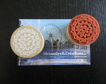 a round wooden rubber stamp depicting a pattern with a flower Center