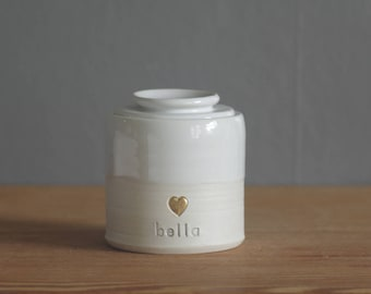 custom urn. gold infilled stamp with ceramic lid, straight shaped urn with custom stamp. modern simple urn for ashes. white customized urn.