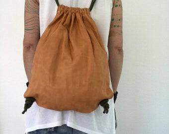 Faded orange washed leather drawstring backpack