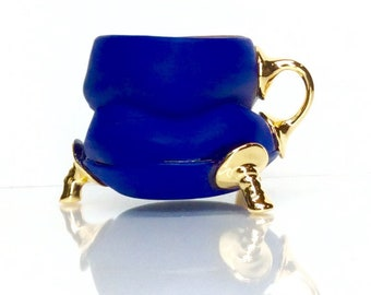 bright blue mug with gold feet and one finger handle