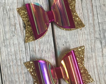 Metallic magenta chunky double stacked bow with gold glitter tails and holographic clear layer