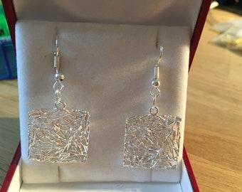 Dangling earrings of silver square shape.